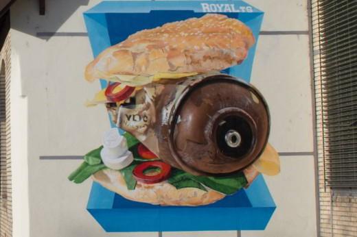 Auf diesem Foto ist ein Graffiti zu sehen. Es ist ein Fast Food Burger mit einer leeren Spraydose anstatt eines Stück Fleisches und rostigen Unterlegscheiben anstatt Tomaten. Guten Appetit!